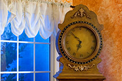 Close up of an antique clock. With roman numerals on the face by an open window Stock Photo