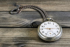 Close up of an antique pocket watch on an antique wooden table Royalty Free Stock Image