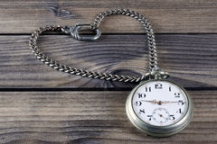 Close up of an antique pocket watch on an antique wooden table Stock Photo