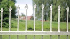Close up of antique wrought iron fence outdoors in the park. Shallow depth of field, spikes on fence.  stock video