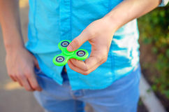Close-up of antistress fidget green spinner in the hand of a you. Ng man. The teenager plays a  spinner on the summer urban outdoors bokeh.  Shallow DOF Royalty Free Stock Photography