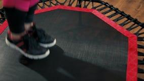 Close up aos pés nas sapatilhas que saltam no trampolim na classe da aptidão no Gym video estoque