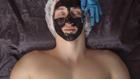 Close-up Aplicando uma máscara cosmética preta à cara de uma pessoa bonita nos termas Foto de Stock
