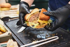 Close up of appetising beef burger. Chef`s hands divide into half cooked hamburgers from beef. Street food ready to. Serve on a food stall. Chef cooks an stock photos