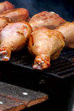 Close-up of appetizing turkey drumsticks grilling on charcoal stove with fire and smoke, selective focus Royalty Free Stock Photography