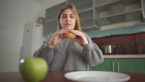 Close up apple and burger lying in front of chubby girl. Young woman takes hamburger first, but puts it pack on the stock video