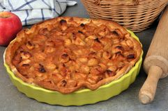 Apple pie in a dish. Close-up of an apple pie beside a rolling pin royalty free stock photos