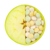 Close up of apple and pills isolated Stock Photography