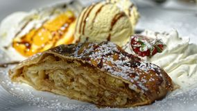 Apple strudel with whipped cream and ice cream. Close-up of Apple strudel with its layers made of cooking apples, served with whipped cream and Vanilla ice cream stock photos