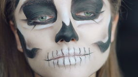 Close up of apply make-up the girl in the form of skull. In full HD stock video footage