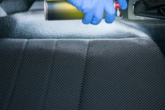 Close-up, applying foam to clean the car seat stock image