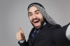 Close up of arabian muslim businessman in keffiyeh kafiya ring igal agal black suit isolated on gray background