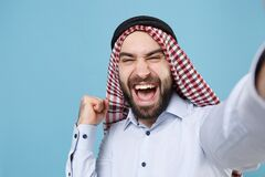 Close up of arabian muslim man in keffiyeh kafiya ring igal agal casual clothes isolated on pastel blue background