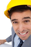 Close up of architect with hard hat grimacing while holding plan Royalty Free Stock Photos