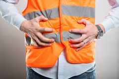 Close-up of architect holding belly like hurting. On gray background Stock Photography