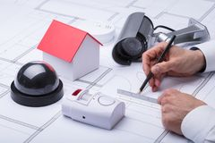 Close-up Of An Architect`s Hand Drawing Blueprint. Near Security Equipments And House Model stock images
