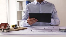 Close up of architect with tablet pc and blueprint stock video