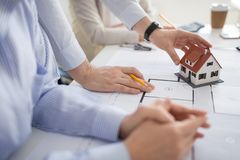 Close up of architects discussing house project. Architecture, construction business and people concept - close up of architects with blueprint discussing house royalty free stock images
