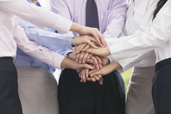 Close up on arm and hands of group of business people with hands on top of each other, cheering Royalty Free Stock Images