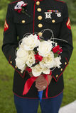 Close up of Army soldier groom holding bride's bouquet. Royalty Free Stock Photos