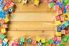 Close up arrangement of alphabet on wooden background. Royalty Free Stock Photos