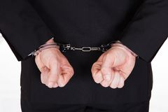 Close-up of arrested businessman. Rear view of arrested businessman with handcuffs Royalty Free Stock Image