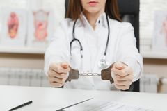 Close up arrested female doctor sitting at desk with medical documents in light office in hospital. Woman in medical stock photography