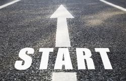 Close up of arrow and word start on asphalt road stock photo