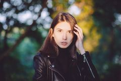 Close up art portrait of a young pretty brunette woman posing outdoors in black leather coat in golden sunlight evening spot Royalty Free Stock Photos