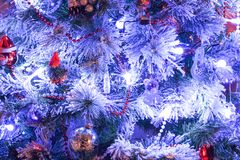 Close-up of an artificial christmas tree in white with cute red and transparent decorations stock photos
