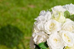 Artificial or Fake White Rose Flower bouquet. Close up Artificial or Fake White Rose Flower bouquet and have Blur of green lawn is background , copy space stock photos
