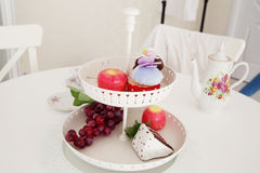 Close-up of artificial grape bunches, apple and cake in white  p Stock Photo