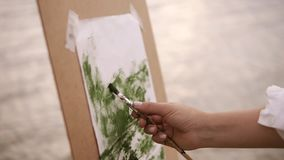 Close up of a artist female`s hand mixing paints on palette and applies it on her surface on easel. Working process. Outdoors stock video footage