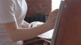 Artist hands holding palette and brush, painting picture close up. Art, creativity, hobby concept. Close up on artist hands with brush painting picture on an stock video