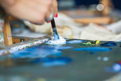 Artist mixes oil paints on pallet Royalty Free Stock Photos