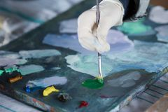 Artist mixes oil paints on pallet. Close-up of artist mixes oil paints on pallet. oil paint brush in hand stock photo
