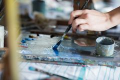 Artist mixes oil paints on pallet. Close-up of artist mixes oil paints on pallet. oil paint brush in hand stock photos