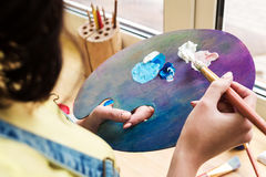 Close-up artist mixes paint brush on an easel Stock Photography