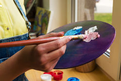 Close-up artist mixes paint brush on an easel Royalty Free Stock Photo