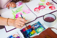 Close-up of the artist draws. A close-up artist paints in the album for drawing a thin wooden tassel of pink flowers with watercolor, on the table lies a leather Royalty Free Stock Photo
