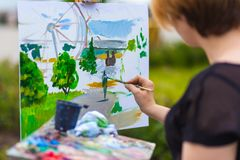 A close-up artist paints. A young blonde female artist in a black T-shirt and jeans paints on canvas and an easel with oil paints in a city park on a sunny day royalty free stock photos