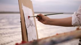 Close up of an artist`s art process. An easel and palette. Girl is putting some color paints on canvas. Blurred lake. Surround on the background stock video