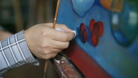 Close-up of artist`s hand smearing oil paints on canvas picture in art workshop. Close-up of male artist`shand smearing oil paints on canvas picture in art stock video footage