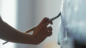 Close-up of the artist`s hands holds a brush and paint on canvas oil. HD stock footage