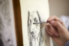 Close Up Of Artist Sitting At Easel Drawing Picture Of Dog In Charcoal stock photos