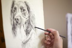 Close Up Of Artist Sitting At Easel Drawing Picture Of Dog In Charcoal stock images