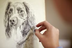 Close Up Of Artist Sitting At Easel Drawing Picture Of Dog In Charcoal royalty free stock photography