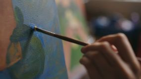 Close-up of artist woman`s hand with brush painting still life picture on canvas in art studio. Indoors stock video footage