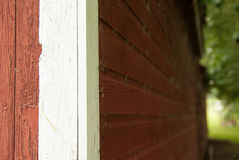 A Close Up Artsy Shot of a Red Barn Wall With White Trim Stock Photo