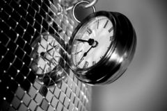 Close up arty shot of a metal large pocket watch clock next to a silver disco ball in black and white. A close up arty shot of a metal large pocket watch clock royalty free stock image